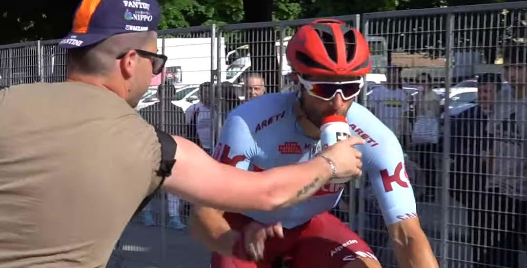 Un espectador arranca la botella de la boca del ciclista Marco Haller. 5