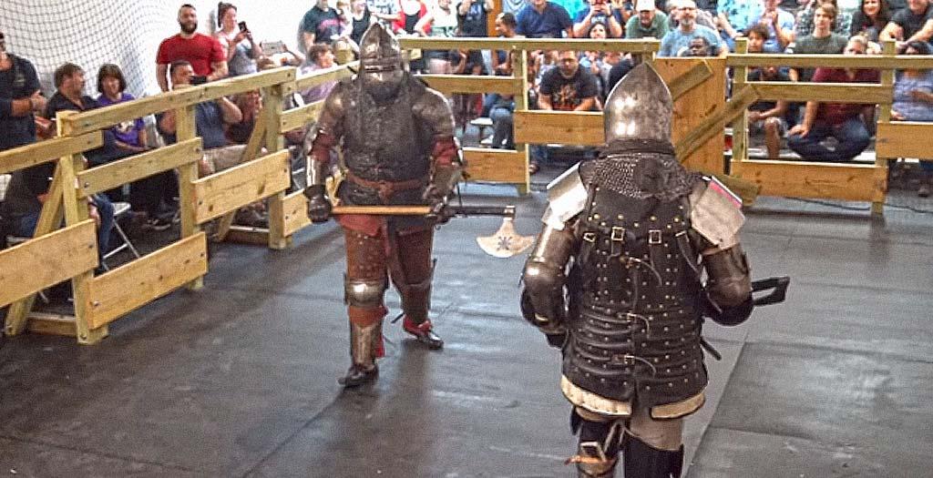 Dos tipos con armadura luchan con hachas como en la edad media 6
