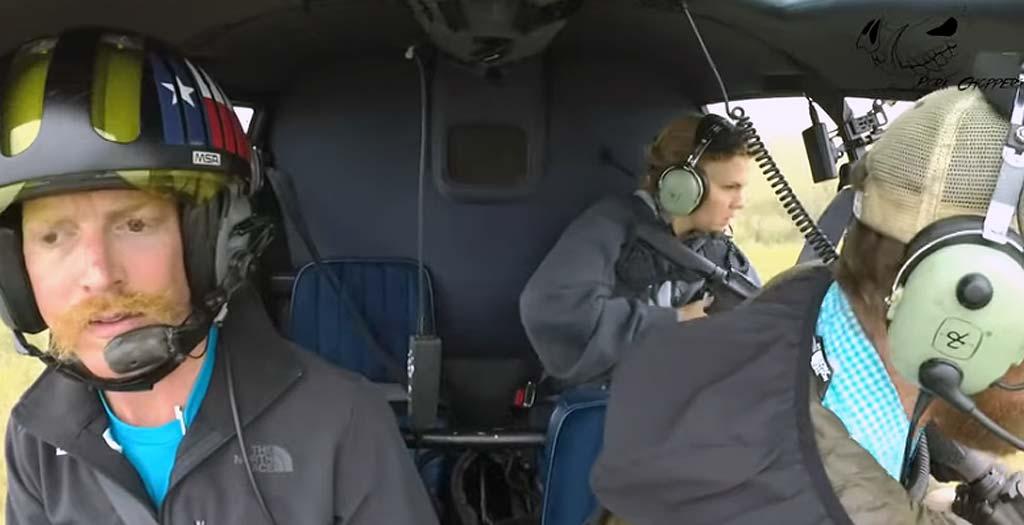 Pareja cazando desde un helicóptero con armas automáticas 2